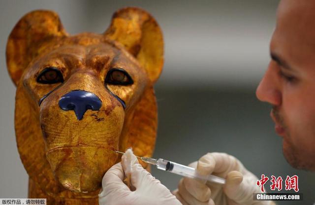 当地时间2018年1月30日,在埃及开罗郊区的大埃及博物馆内,考古专家们正在修复图坦卡蒙法老时期的文物。图为技术人员用化学试剂来修复图坦卡蒙法老床上的一个动物雕塑。