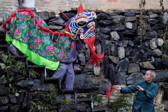 """1月9日,湖南吉首市矮寨镇大兴社区村民时元高在表演""""斗狮""""。73岁的时元高是""""苗乡雄狮""""舞狮队队长,在队中扮演""""斗狮者""""。"""