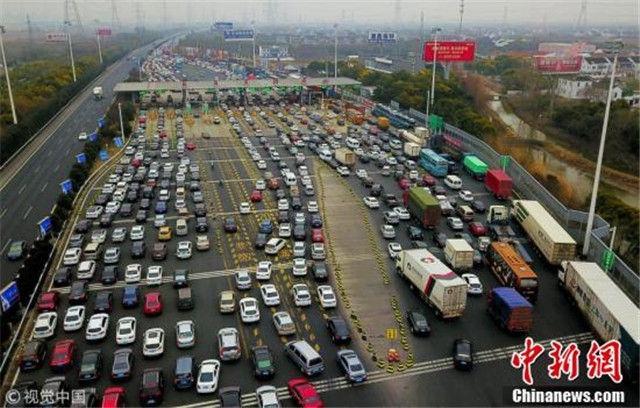 ↑2月10日,由上海市区驶出前往山东、江苏苏北方向的车流在沈海高速苏通大桥南收费站附近排起了长龙。