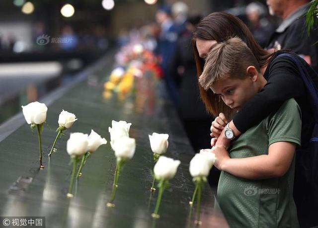 2018年9月11日,一名小男孩和他的母亲在纪念911恐怖袭击17周年的纪念活动中向归零地眺望。