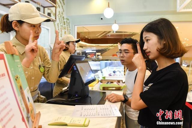 """4月14日,广州""""无声""""面包店的收银员通过手势比划与顾客交流。这家""""无声""""面包店的收银员、咖啡师、西点师等17名员工均为聋哑人士,他们通过手势、卡片、写字等方式与顾客沟通,在面包店内创造属于自己的价值。中新社记者 陈骥旻 摄"""