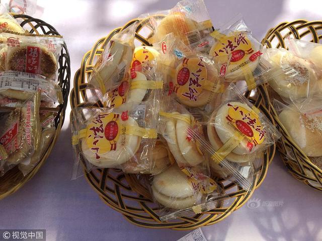 """2018年3月10日,70岁的黄茂才师傅在武汉吉庆街春节庙会上展示他用泡沫制作的仿真艺术品,吸引了很多游客驻足围观。黄茂才师傅制作的饼干,外面的包装纸和""""饼干""""上面的白色芝麻,再加上微黄的饼干底色,很多游客最初看见时都以为这就是真正的饼干,经提醒后细看才发现是假饼干。"""