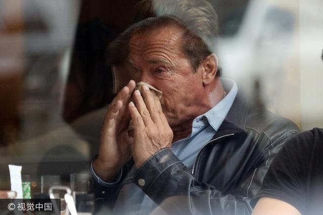 当地时间2017年9月13日,比弗利山庄,阿诺德·施瓦辛格(Arnold Schwarzenegger)和儿子帕特里克·施瓦辛格(Patrick Schwarzenegger)一起吃早餐。阿诺德·施瓦辛格似感冒,不停擤鼻涕擦眼泪。