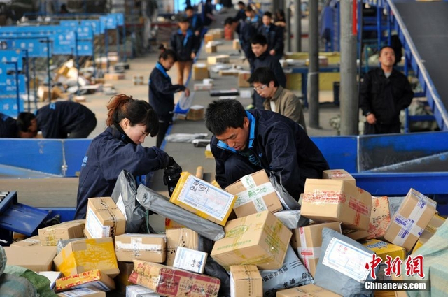 """2013年11月12日,""""双十一""""全民网购狂欢节后,山西太原的快递人员正在分拣大量包裹。 中新社记者 韦亮 摄"""