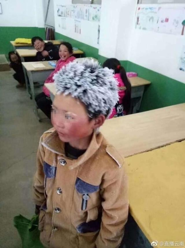 """1月9日,云南昭通一名头顶风霜上学的孩子照片在网上引起广泛关注,照片中的孩子站在教室中,头发和眉毛已经被风霜粘成雪白,脸蛋通红,穿着并不厚实的衣服,身后的同学看着他的""""冰花""""造型大笑。经核实,""""冰花""""男孩系鲁甸县新街镇转山包小学三年级的学生,因当天气温较低,家离学校太远,走路来上学沾染冰霜导致。图:直播云南"""