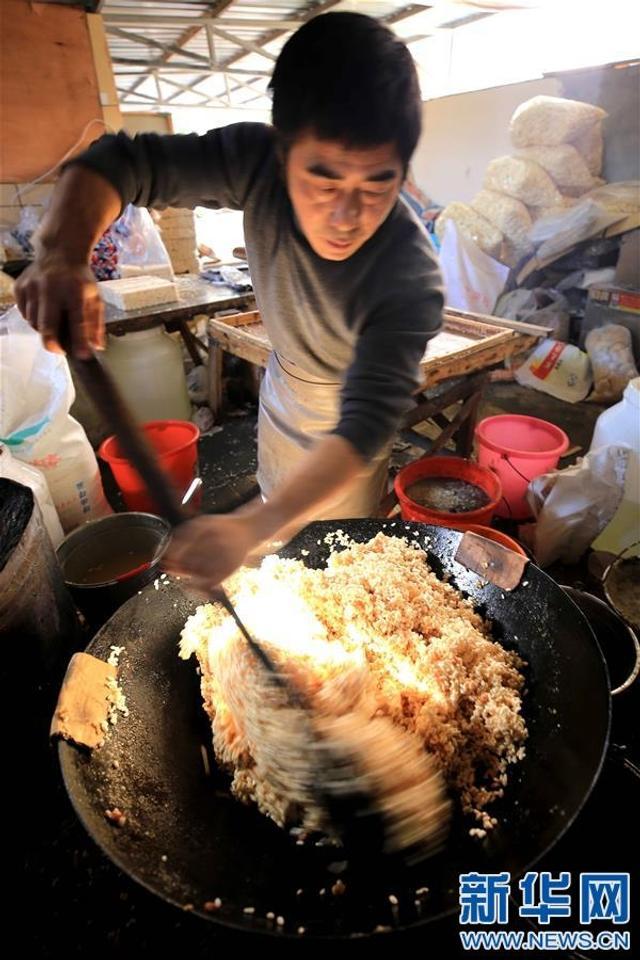 12月22日,在江西省靖安县香田村,一名村民在制作米花糖。当日是冬至节气,江西靖安有冬至制作米花糖的传统习俗,家家户户用爆米花和熬化的麦芽糖制作米花糖,希望来年生活如糖一样甜蜜。新华社发(徐仲庭 摄)