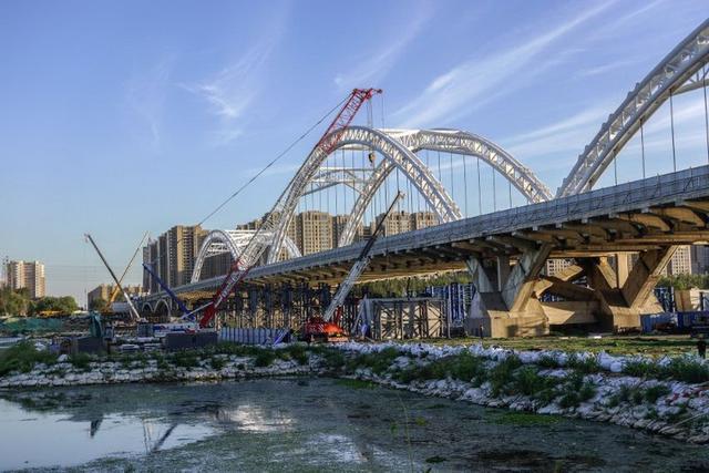 走进长青桥施工现场,打桩机等大型机器随处可见,工人们热火朝天地忙活着,这边儿还在起吊,那边儿又忙打桩……  近日,记者走进作为沈阳东部快速路系统重要节点工程的长青跨浑河桥加宽改造项目现场,看到该桥下部结构及墩身施工接近尾声,即将开始上部钢箱梁架设施工。