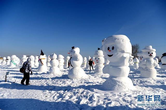 1月11日,游客在哈尔滨外滩赏冰乐雪园的奇趣雪人谷园区内观赏形态各异的雪人雕塑。当日,2018座雪人雕塑在哈尔滨外滩赏冰乐雪园的奇趣雪人谷园区内展出,吸引来自各地的游客前来观赏。