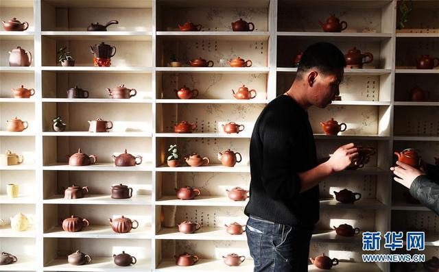 孙宏凯向顾客介绍紫砂产品(4月12日摄)。孙宏凯是辽宁省朝阳市喀左县南公营子镇王爷府村人,1993年出生的他两年前成立了自己的隆源紫砂壶工作室,聘请宜兴制壶多年的师傅做老师,同时招聘20多名本地的制壶师加盟。