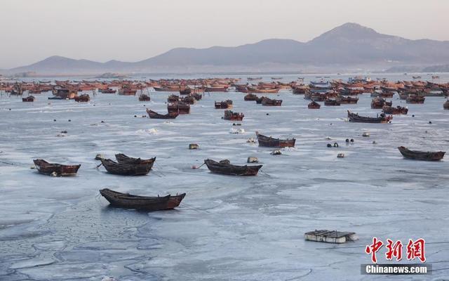 """2月11日,辽宁省大连市金石滩渔港,结冰海域中的渔船被""""冰封""""。受持续低温天气影响,黄渤海进入了本年度严重冰期,给渔业生产带来不利影响。"""