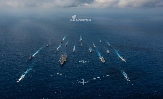 """美日两国近日在关岛附近海域举行了大规模海空联合军演,在军演最后一天,美国海军和日本海上自卫队的18艘舰艇(包括里根号航母和日向号直升机驱逐舰)组成海上编队同美日战机拍合影。此次演习美日派出包括数百架战机和数十艘军舰的强大兵力。这一演习规模甚至超过了目前北约号称自冷战结束以来规模最大的""""三叉戟接点-2018""""演习。(图片来源:lfx160219)"""