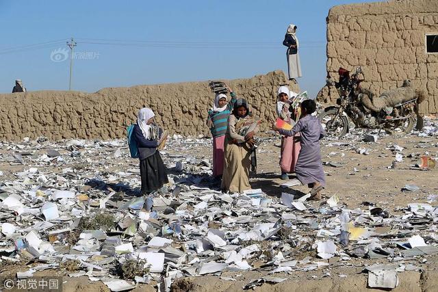 当地时间2018年1月13日,也门萨达,当地一所储存学校教材的仓库遭空袭炸毁,学生在废墟中捡拾教材。图:视觉中国 NAIF RAHMA/摄