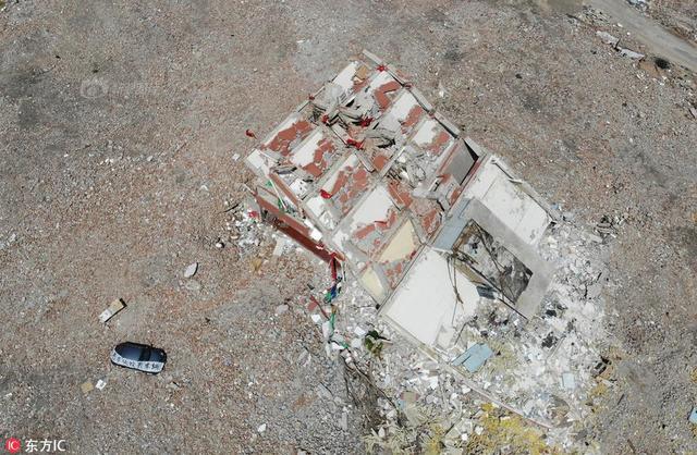 2018年6月12日,山西省太原市,松庄城中村改造工地,一栋建筑孤零零的立在废墟之中。令人吃惊的是,该栋房屋已经倒塌过半,而且随时都有继续倒塌的危险,但仍然有人在其内部居住生活。供图:东方IC