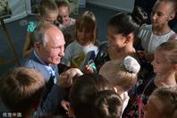 俄总统普京出席活动单膝下跪亲吻小萝莉