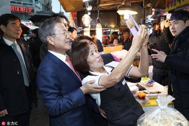 当地时间2018年11月8日,韩国浦项市,韩国总统文在寅走访浦项市一菜市场,与民众热情互动。图为文在寅与大妈合影自拍。来源:东方IC
