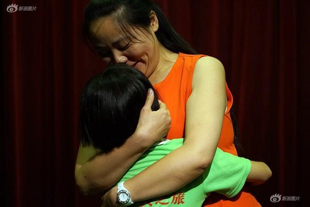 2017年7月,河南省新蔡县30名留守娃在老师的带领下,奔赴千里之外的北京,与打工的父母团聚。这是7月12日下午,河南省新蔡县农村留守儿童赴京与父母团聚之旅见面会后举行了孩子成长汇报演出。杜欣欣作为留守儿童的代表上台朗读了给妈妈的信,母女紧紧地拥抱在一起。摄影|周一渤