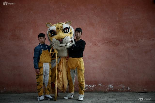 """数百年来,作为习武之乡,陈家沟的功夫代代相传,在陈家沟有着""""喝了陈沟水,都会翘翘腿""""的说法。代表着陈家沟荣耀的舞虎,也代代传了下来。因为是习武之乡,舞虎的难度不断提高。2019年1月1日,河南温县陈家沟村,舞老虎的两个男孩。去年冬季后,村里老拳师就开始组织十余名青少年太极拳爱好者训练舞虎,并将于春节期间巡回表演闹新春。摄影 柳涛"""