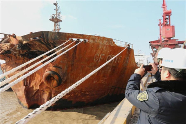 """1月10日12时30分,在中国东海海域碰撞起火的中国香港籍散货船""""CFCRYSTAL长峰水晶""""靠泊浙江省舟山市,当地检验检疫部门紧急对其进行现场检疫。"""