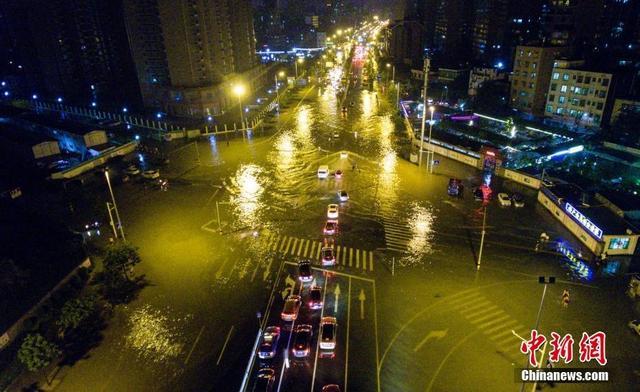 """11月14日下午,受弱冷空气和偏东气流影响,海南省海口市普降暴雨,局地大暴雨。暴雨导致该市多条道路积水严重出现内涝,一片""""汪洋""""成""""泽国"""",交通几乎瘫痪。图为海口市红城湖路积水严重,车辆水中冒险通行如开船。中新社记者骆云飞摄"""