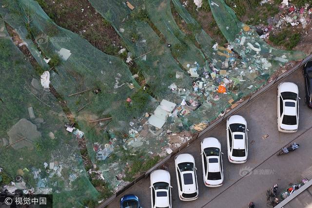 """2017年5月19日,河南郑州,御府三期小区一多半区域被围挡圈起,里面是一两米深的大土坑,堆着垃圾等杂物,占地儿、味儿臭、招蚊子不说,一到下雨天还会有积水。从2010年前后小区交房到现在,人防工程一直没建起来,这个""""垃圾坑""""存在了七年有余。图片来源:视觉中国"""