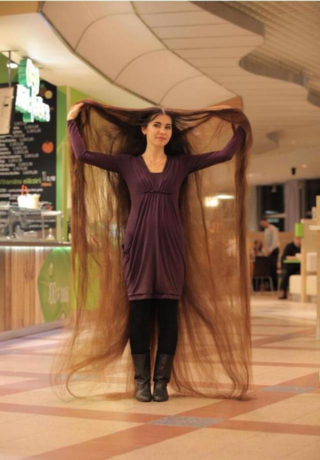 AliiaNasyrova是一位27岁的姑娘,她来自拉脱维亚。二十年来,Aliia从来没有剪过自己的头发,头发的长度达到了7.5英尺(约2.3米),重量甚至超过了她家的猫的体重。(上图是Aliia举起了她两米多长的头发)