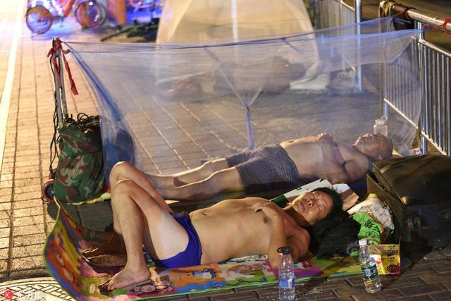 南京酷暑难耐 农民工为省钱自带蚊帐打赤膊成排睡大街