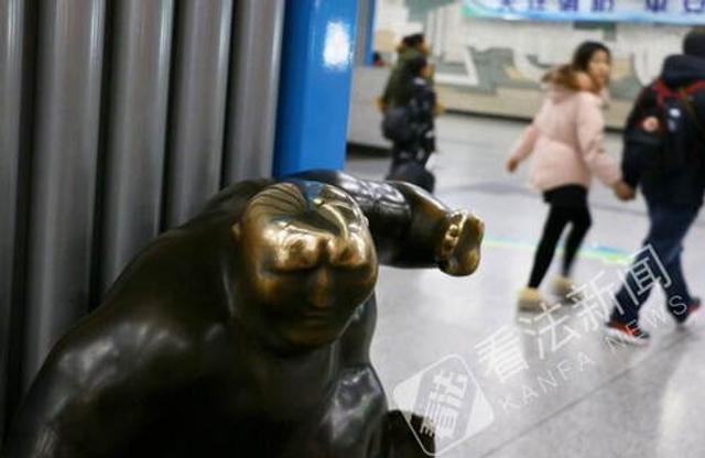 """近日,据微博网友爆料,北京地铁4号线国家图书馆站内的铜像被""""摸得光溜""""。1月13日上午,法制晚报·看法新闻记者来到该站探访看到,车站换乘厅内摆放了两件蒙古族特色的雕塑艺术品《坐》和《摔跤》,其中《摔跤》铜人的头顶已经被人摸出了黄铜,十分锃亮。在换乘的五分钟内,有十多位乘客路过时都摸了一下雕塑的头顶,有些乘客还停留下来上前观赏。摄影/宫主"""
