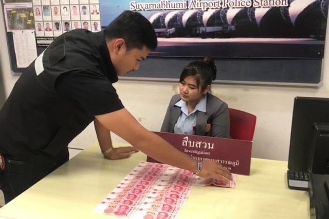 3月12日下午,在泰国素万那普机场内,1名26岁的泰国女行李安检员因被举报偷盗游客财物在国际出发口行李安检处被捕,警方还从其外衣右边口袋里缴获40张100元人民币现金的赃物。来源:泰国头条新闻