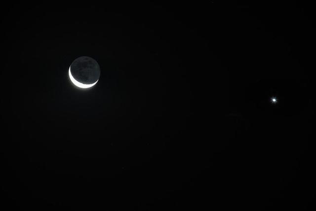 """2018年12月4日,北京,天宇上演""""金星合月"""",清晨5点时,东南方低空出现一颗明亮的金星和一弯窄月近距离相依相伴的美丽画面。金星位于月亮以南3.6度左右的位置上。在这个时间附近,以肉眼从地面看去,金星与月亮的二维距离在夜空中看起来是比较接近的,但是在三维空间上,它们的距离是非常遥远的(大约6000万千米)。"""