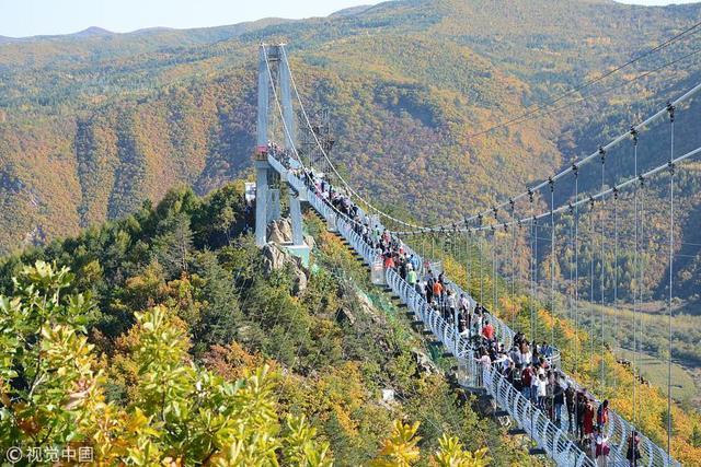 2018年10月4日,游客在吉林延吉龙井琵岩山5D玻璃吊桥上体验游玩。这处玻璃桥带有破裂音效,前来游玩的游客直呼刺激。
