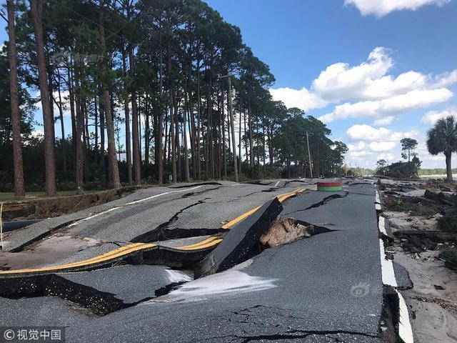 """当地时间2018年10月11日,美国佛罗里达州卡拉贝尔,当地遭4级飓风""""迈克尔""""袭击后路面裂开,输电线受损,工人抓紧恢复电力。"""