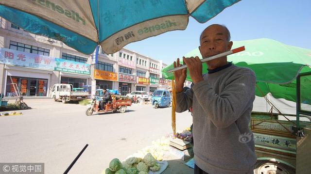 """2018年10月10日,在山东禹城70岁的张秀阳是王庄街蔬菜商贩中的""""明星"""",最早人们的记忆是这位老汉喜欢吹唢呐,后来改成了吹笛子。在张秀阳的聊天中得知,他从小喜欢乐器但家里情况一般也从来没特地买过乐器,就拿手中的这个笛子来说还是自己亲手做的。这个原本是个铝铁管子被老张钻上孔,在废弃的灯笼上摘了个黄穗头老张的铁笛子就成了。"""