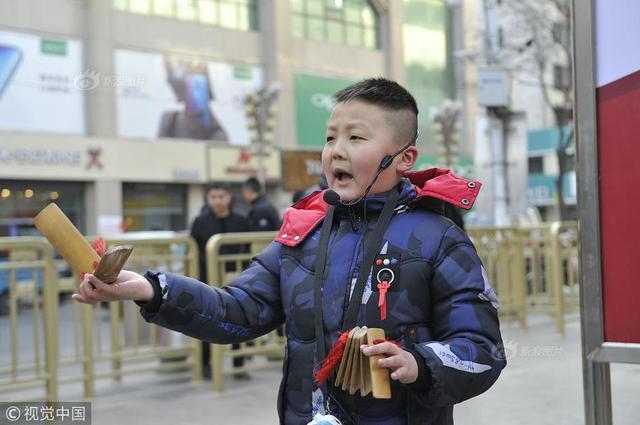 2019年1月9日,在银川市鼓楼步行街,9岁的刘宁波小朋友正在街头表演快板。刘宁波小朋友是银川兴庆区第十六小学四年级小学生。他的快板表演技能是从学校里的兴趣班学来的。供图:视觉中国