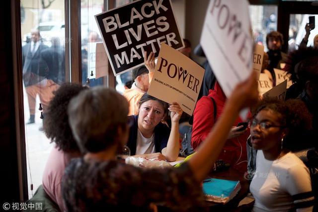 """当地时间2018年4月16日,美国费城,民众抗议星巴克店员报警抓无辜黑人顾客。费城一家星巴克的顾客梅莉萨·德皮诺12日拍摄一段视频并上传社交媒体,显示多名身着制服的警员围住两名坐在店内的黑人顾客,问话后用手铐拷住两人押走。两名黑人没有抵抗。一名白人顾客不停问警察:""""他们到底做了什么?他们做了什么?""""供图:MARK MAKELA/视觉中国"""