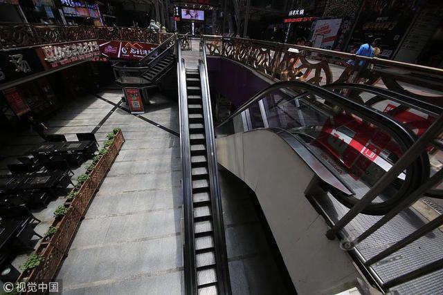 """2018年5月14日,在重庆解放碑得意世界附近,有一部迷你电梯,十分喜感,也显得十分""""苗条""""。 通常而言,一般的电梯,每级阶梯都可以站立两个人,但是这部迷你电梯,占据的空间相对狭窄,每一级阶梯只能容得下一人。供图:苏志刚/视觉中国"""