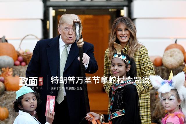 """【示威假新闻?特朗普万圣节拿蛇杖念咒语】当地时间2018年10月28日,华盛顿,美国白宫举办万圣节派对,总统特朗普与夫人梅拉尼娅给萌娃发糖。期间特朗普拿起一女孩的蛇杖,对着媒体念念有词,或是借此示威""""假新闻""""媒体。"""