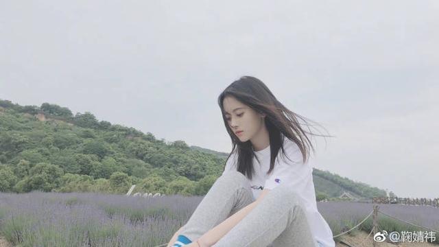 鞠婧祎晒春游照置身花丛,穿白色半袖画面清新唯美。图据微博@鞠婧祎