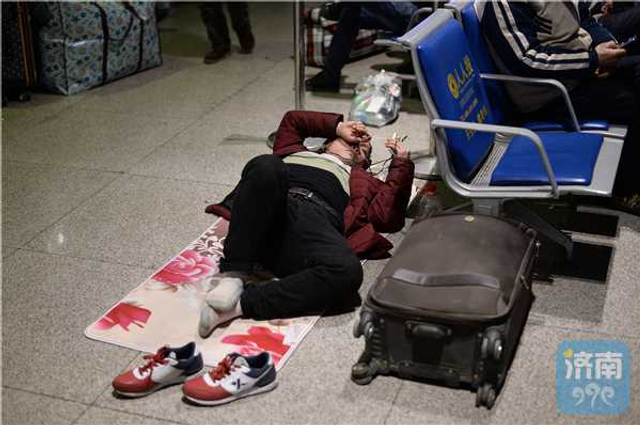 """春节的脚步越来越近,深夜时分火车站候车大厅依然热闹得如同""""不夜城"""",在济南火车站的候车大厅内,乘坐夜间发车的旅客,有的围坐在一起打牌娱乐,有的趴在行李上打盹休息,也有三五成群的农民工怕携带的行李多弄脏候车的乘客,席地而坐,躺卧在行李上。"""