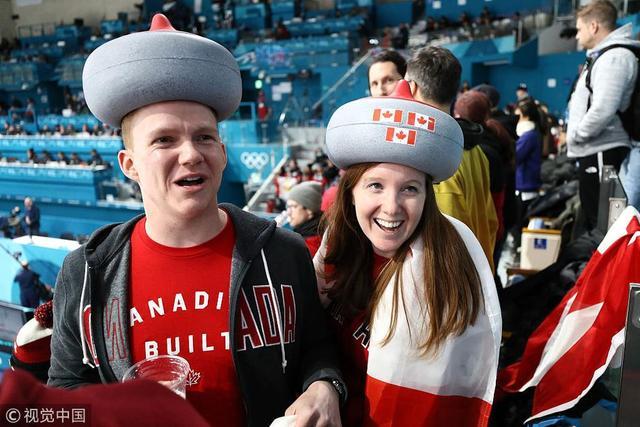 北京时间2月13日,韩国,2018平昌冬奥会冰壶混双决赛加拿大与瑞士队的比赛中,看台上加拿大队粉丝头戴冰壶形状的帽子为主队加油。