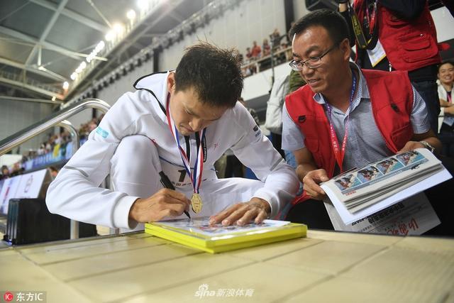 2018年4月15日,山西太原,2018全国游泳冠军赛暨亚运会选拔赛第三个比赛日,颁奖过后的孙杨蹲坐在泳池边为记者粉丝签名留念。
