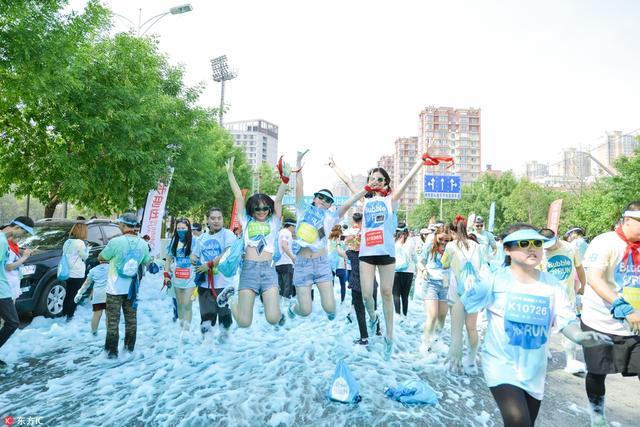 """""""泡泡跑""""连续三年再次来到沈阳,吸引近万名年轻人参加,穿越""""泡泡雨""""和""""泡泡池""""。在炎热的天气里体验泡泡带来的快乐和清凉,称之为地球上比开心更开心的5公里赛事。"""