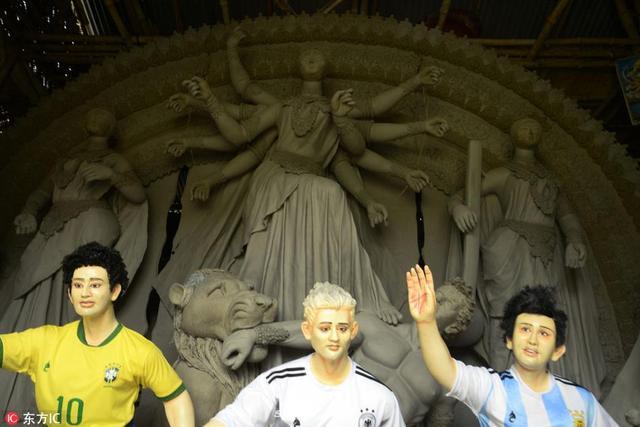 """当地时间2018年6月13日,印度加尔各答,印度艺术家制作世界杯主题雕塑。阿根廷、巴西、德国十号""""面目全非""""。"""