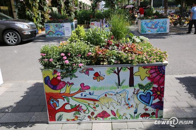 近日,在西安南大街人行道,四方形的花坛四面用儿童画装饰起来。这些画出自众多孩子之手,画出了孩子心中的新西安。