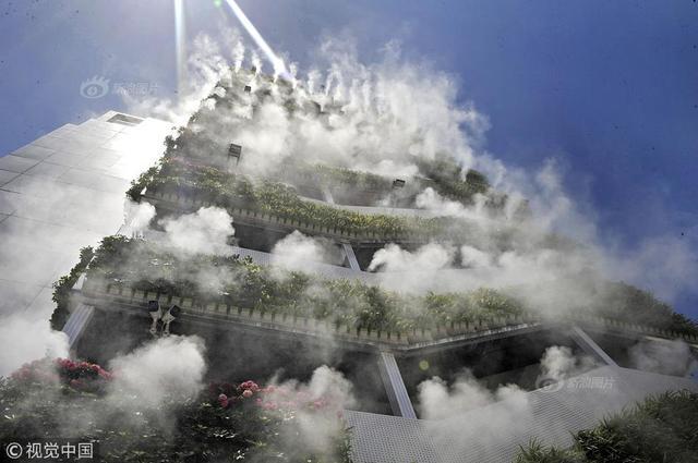 """高楼外长满绿植,还萦绕着雾气。网友评论这是""""第四代住房"""",其实这是西安市众创示范街区的一处安装了智能雾森系统的西北最大户外垂直绿化。高楼垂直绿化高达38米,用16848盆绿植打造,绿化面积450平方米,是目前西北地区最大的户外垂直绿化墙,同时也是国内最大的智慧植物墙。"""