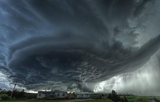 """他们拍摄的照片中,龙卷风的形态体积十分惊人,连高大的建筑都相形见绌。当天气""""暴怒""""时,广袤的大平原上闪电霹雳,风起云涌,撼人心魄。"""