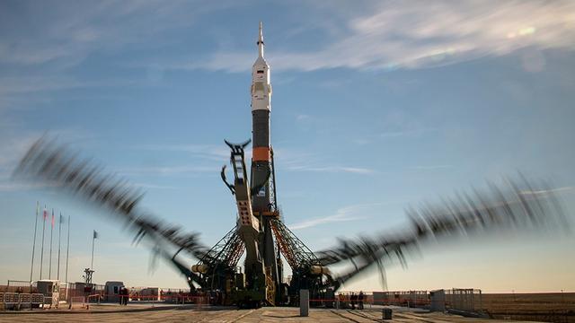 10月9日,哈萨克斯坦的拜科努尔航天发射场,在这张长曝光照片中,可以看到发射台起重架手臂正在将联盟号火箭固定。
