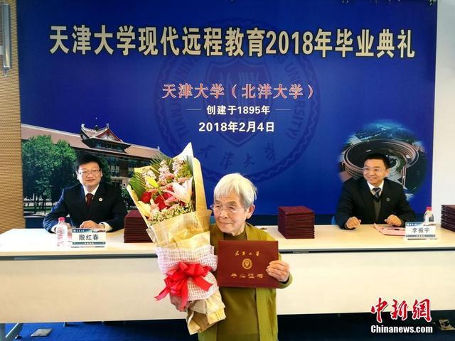 """2月4日,在天津大学卫津路校区,一场毕业典礼格外受关注。81岁的""""奶奶同学""""薛敏修完成了所有专升本课程的学习,在这一天拿到了天津大学现代远程教育的本科毕业证书。图为薛敏修在毕业典礼上。 中新社记者 张道正 摄"""