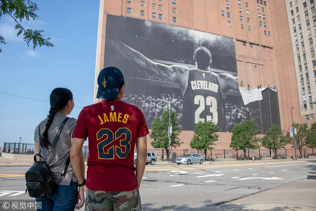 球迷与拆了半角的海报留念——随着勒布朗-詹姆斯加盟洛杉矶湖人队,位于克里夫兰市中心一栋大楼外墙的詹姆斯巨型画像正式被移除。围观球迷们纷纷拿起手机合影留念,纪念一个时代的终结。