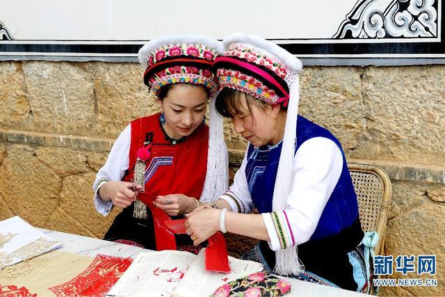 """今年54岁的杨慧英(右)是云南省非物质文化遗产代表性传承人。这名云南省大理市海东镇文武村的普通白族妇女,凭着对本民族文化的热爱,不仅通过剪纸、刺绣让全家过上了幸福生活,也将这门传统手工技艺传授给年轻人,用一双巧手""""剪""""出了精彩人生, """"绣""""出了幸福画卷。"""