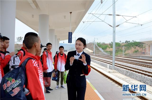 石林西站值班站长李玉书向出行的中学生介绍看车票找车厢和座位号的方法。常婧 摄